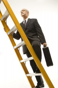 Businessman climbing ladder.